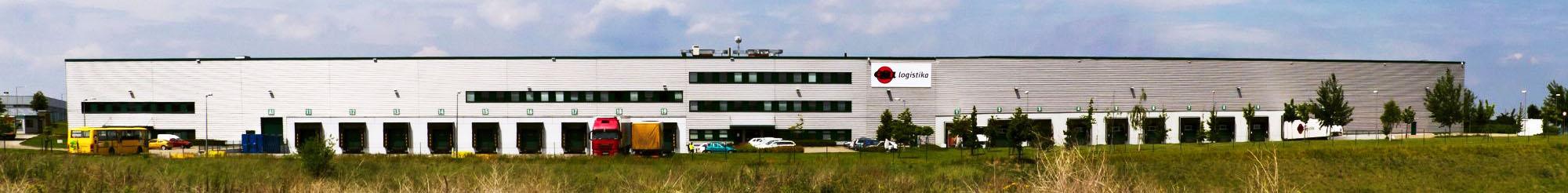 Skladování - budova chlazeného a distribučního skladu v Jažlovicích, přední pohled, logo ESA logistika, rampy, parkoviště, kamiony, zeleň