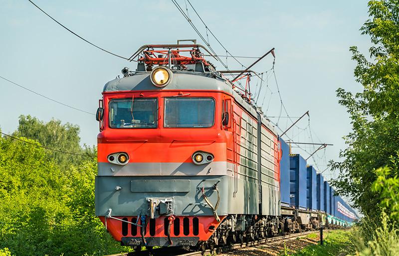 Železniční doprava - přední pohled na elektrickou lokomotivu a kontejnerový vlak projíždějící zelenou krajinou