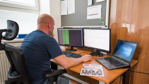 Kamionová doprava vyžaduje i pracovníky v administrativě, na obrázku dispečer v kanceláři, řídící silniční přepravy pomocí softwérového systému TMA.
