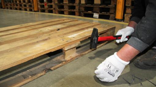 Prodej palet. Opravy palet - pracovník opravující paletu pomocí kladiva a hřebů.