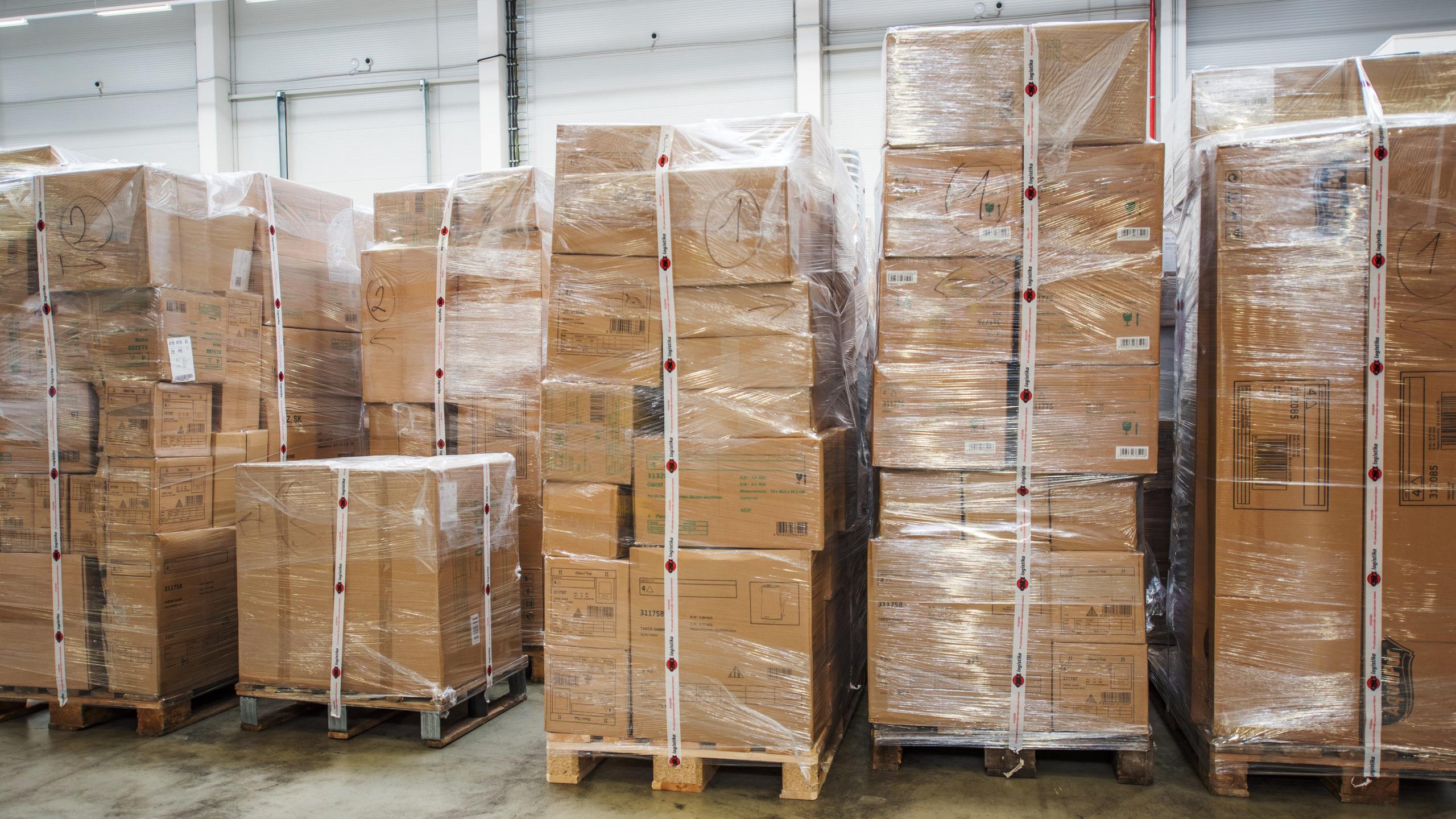 Celní deklarace pohled do celního skladu. Pracovník celního skladu provádí kontrolu uloženého materiálu.